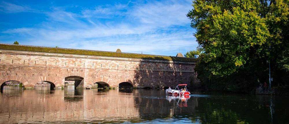 Lors d'une balade entre amis en bateau électrique à Strasbourg, découvrez le barrage Vauban