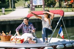 Couple prenant l'apéritif à bord d'un bateau électrique